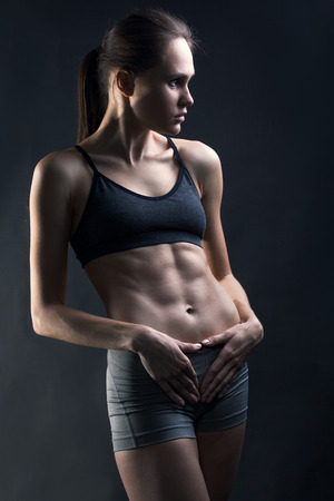 middle eastern ethnicity: Close up image of middle eastern female in sports clothing relaxing after workout on grey background. Muscular female body with sweat. Image with copyspace for text