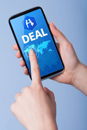 technology deal: Man presses a touch screen smart phone with the symbol of an deal. Business, technology, internet concept.