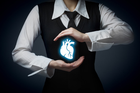 health symbols metaphors: Protect health (healthcare) and heart problems prevention (cardiology) concept. Cardiologist with protective gesture and symbol of heart and ECG heartbeat. Stock Photo