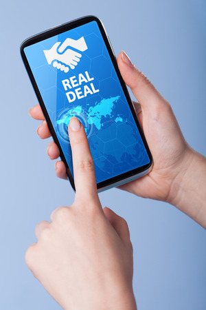 technology deal: Man presses a touch screen smart phone with the symbol of an real deal. Business, technology, internet concept.
