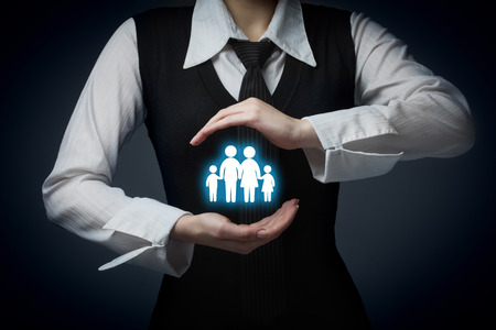 Insurance concept, family life and property insurance, family services and supporting families concepts. Businessman with protective gesture and silhouette representing young family and house.