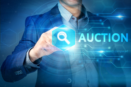 auctioneer: Business, internet, technology concept. Businessman chooses Auction button on a touch screen interface.