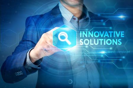 Affaires, internet, concept technologique. Homme d'affaires choisit bouton Solutions innovantes sur une interface à écran tactile.