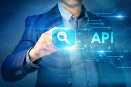 api: Business, internet, technology concept.Businessman chooses API button on a touch screen interface. Stock Photo