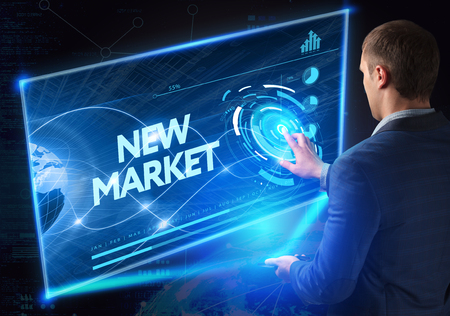 technology market: Business, Technology, Internet and network concept. Technology future. Young businessman, working on the smartphone of the future, clicks on the virtual display button: New Market