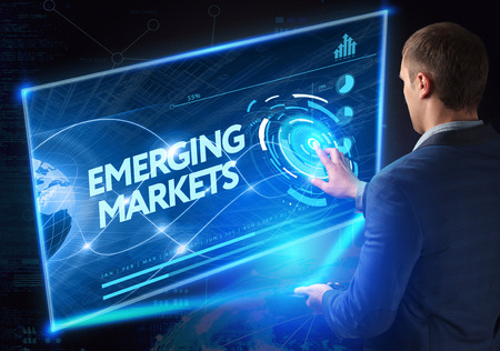 emerging markets: Business, Technology, Internet and network concept. Technology future. Young businessman, working on the smartphone of the future, clicks on the virtual display button: Emerging Markets Stock Photo