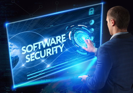 security technology: Business, Technology, Internet and network concept. Technology future. Young businessman, working on the smartphone of the future, clicks on the virtual display button: Software Security Stock Photo
