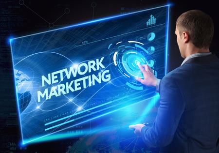 redes de mercadeo: Negocio, Tecnología, Internet y el concepto de red. la tecnología del futuro. Joven empresario, que trabaja en el teléfono inteligente del futuro, hace clic en el botón de pantalla virtual: la red de comercialización Foto de archivo