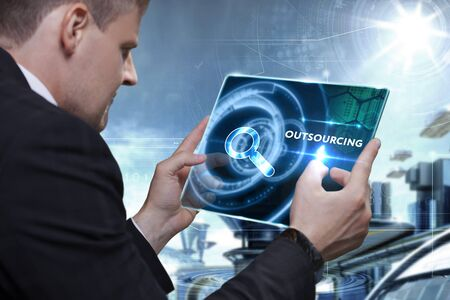 offshoring: Business, Technology, Internet and network concept. Businessman working on the tablet of the future, select on the virtual display: outsourcing