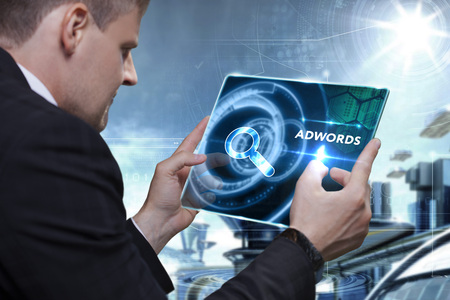 adwords: Business, Technology, Internet and network concept. Businessman working on the tablet of the future, select on the virtual display: AdWords Stock Photo