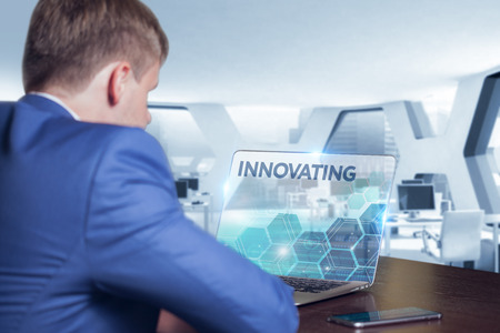 innovating: Business, Technology, Internet and network concept. Business man working on the tablet of the future, select on the virtual display: Innovating
