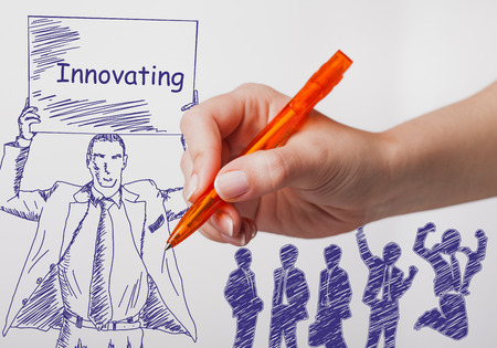 innovating: Business, technology, internet and networking concept. The girl draws a pen businessman with a poster in his hands. The sign reads: Innovating Stock Photo