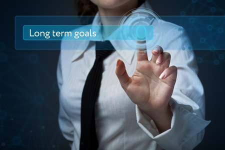 Business, technology, internet and networking concept. Business woman presses a button on the virtual screen: Long term goals Stock Photo