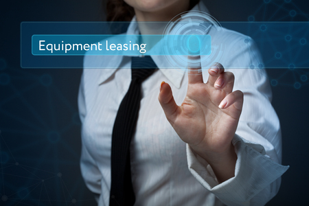 Business, technology, internet and networking concept. Business woman presses a button on the virtual screen: Equipment leasing Stock Photo