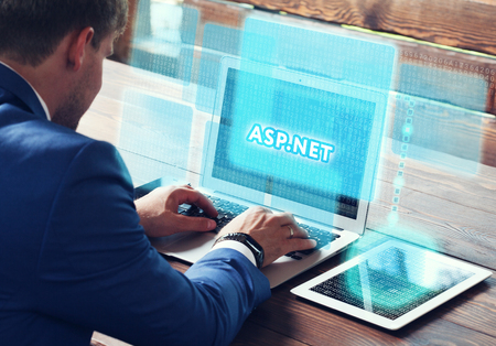 asp: Business, technology, internet and networking concept. Young businessman working on his laptop in the office, select the icon ASP.NET on the virtual display. Stock Photo