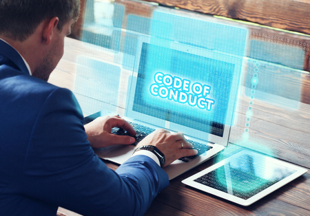 work ethic responsibilities: Business, technology, internet and networking concept. Young businessman working on his laptop in the office, select the icon Code of conduct on the virtual display. Stock Photo