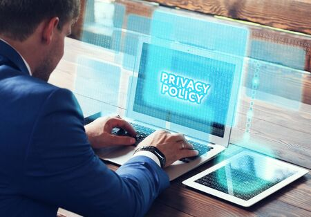 classified: Business, technology, internet and networking concept. Young businessman working on his laptop in the office, select the icon Privacy policy on the virtual display.