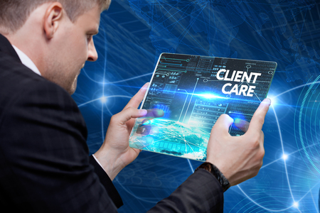Business, technology, internet and networking concept. Young businessman working on his laptop in the office, select the icon client care on the virtual display. Imagens