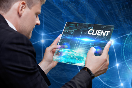 Business, technology, internet and networking concept. Young businessman working on his laptop in the office, select the icon client on the virtual display.
