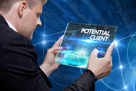 Business, technology, internet and networking concept. Young businessman working on his laptop in the office, select the icon potential client on the virtual display. Imagens