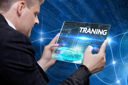 Business, technology, internet and networking concept. Young businessman working on his laptop in the office, select the icon traning on the virtual display.