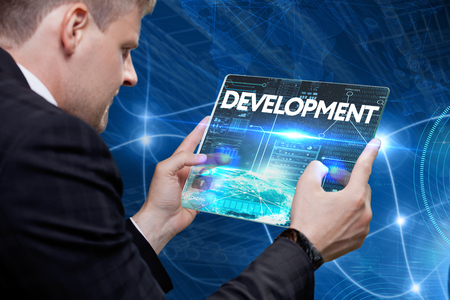 Business, technology, internet and networking concept. Young businessman working on his laptop in the office, select the icon development on the virtual display.