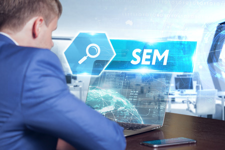 Business, technology, internet and networking concept. Young businessman working on his laptop in the office, select the icon SEM on the virtual display.
