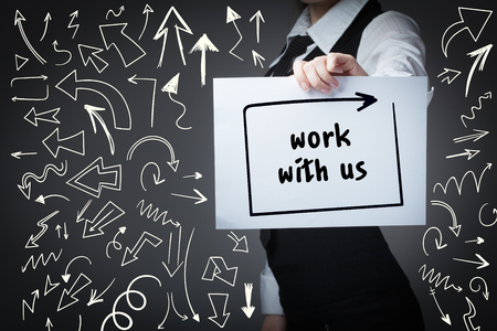 advertise with us: Technology, internet, business and marketing. Young business woman writing word: work with us Stock Photo