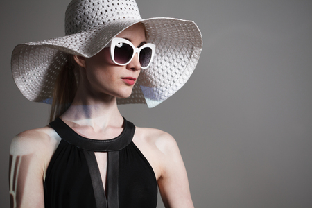 Young beautiful fashionable woman with trendy makeup. Model looking at camera, wearing stylish eyeglasses, hat. Female fashion, beauty concept Stock Photo - 124760067