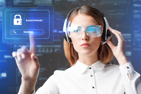 Business, Technology, Internet and network concept. Technology future. Young businesswoman working in virtual glasses, select the icon RANSOMWARE on the virtual display. Stock Photo