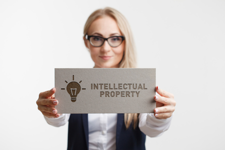 questions: Business, Technology, Internet and network concept. Young girl holding a sign with an inscription intellectual property Stock Photo
