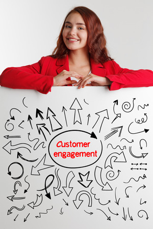 niche: Technology, internet, business and marketing. Young business woman writing word: customer engagement