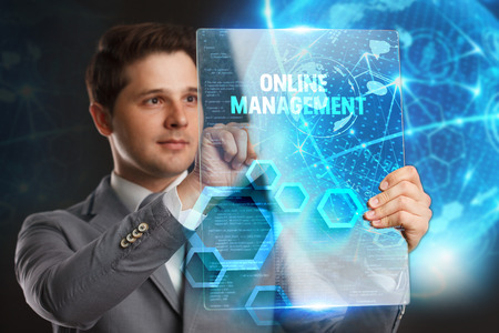 Business, Technology, Internet and network concept. Young businessman showing a word in a virtual tablet of the future:Online management Stock Photo