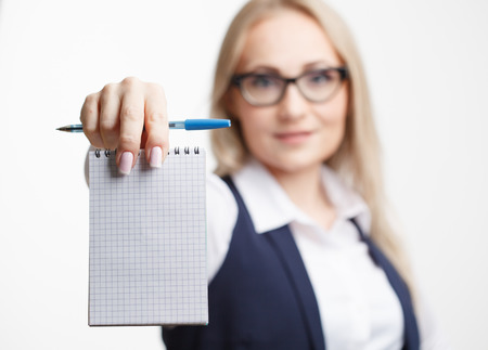 Businesswoman with notepad or organizer shows something. On a white background