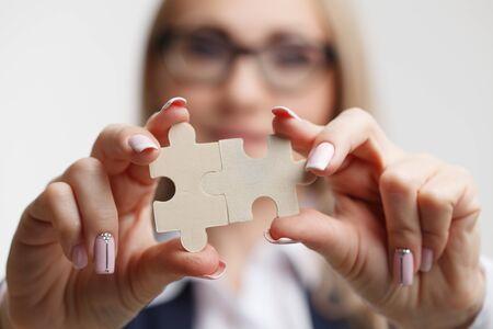 Portrait. Business woman connecting puzzle pieces.