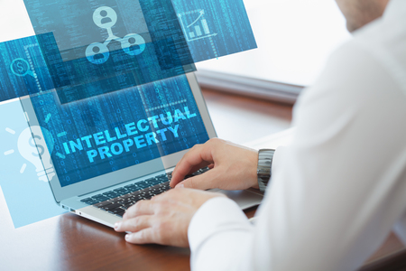 Business, technology, internet and networking concept. Young businessman working on his laptop in the office, select the icon Intellectual property  on the virtual display.