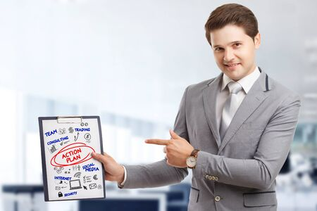 Planning marketing strategy. Business, Technology, Internet and network concept. Young businessman shows the word: Action plan Stock Photo