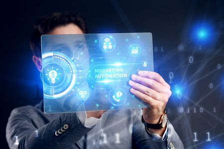 Planning marketing strategy. Business, Technology, Internet and network concept. Businessman working on the tablet of the future, select on the virtual display: Marketing automation Stock Photo