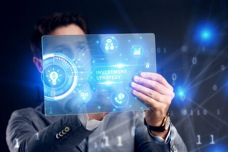 Planning marketing strategy. Business, Technology, Internet and network concept. Businessman working on the tablet of the future, select on the virtual display: Investment strategy Stock Photo