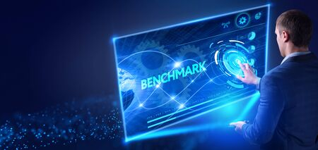 Business, Technology, Internet and network concept. Young businessman working on a virtual screen of the future and sees the inscription: Benchmark