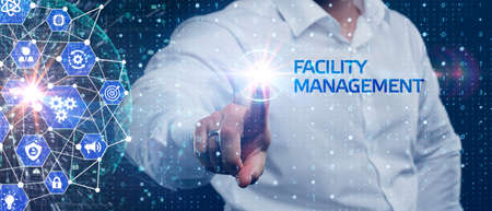 Business, Technology, Internet and network concept. Young businessman shows the word on the virtual display of the future: Facility management Banco de Imagens