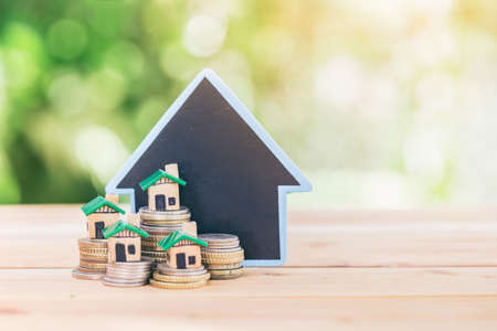 The house placed on a coin is like a village or condo. planning savings money of coins to buy a home concept, concept for property ladder, mortgage and real estate investment or saving for a house.