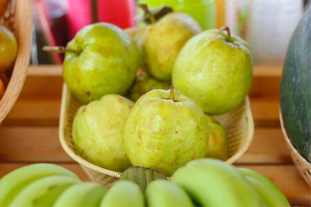 guava In wood basket on wood table or shelf at the market street in Thailand. Select focus.