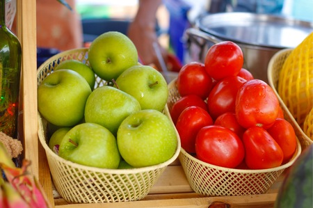 Green apple and tomatoes on the wood basket at the market in Thailand.