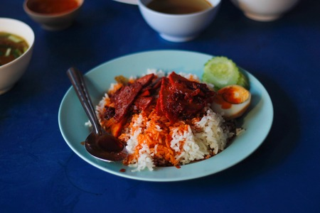 Barbecued red pork in sauce with rice With egg and cucumber.on blue dish.select focus. Stok Fotoğraf