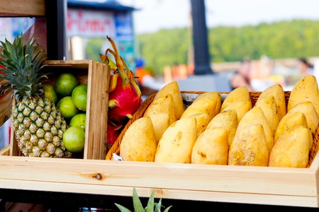 Yellow mangoes,pineapple, lime on wood basket and shelf at market street in Thailand.