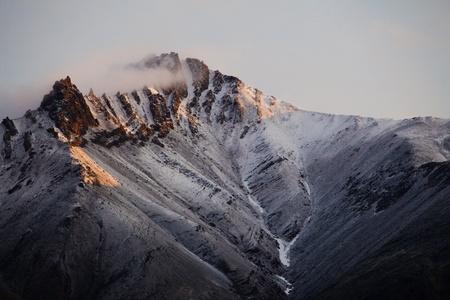 Snow covered mountain peak from Brooks Mountain Range in Northern Alaska photo