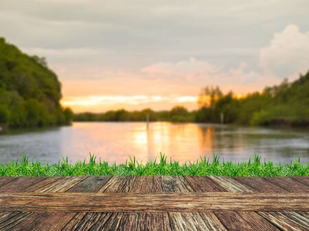 green river: Empty wooden table and grass with river and muontain natural bokeh background. Product display template.