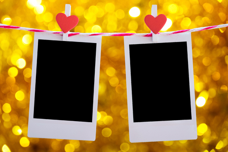 pack string: 2 Blank instant photo and red clip paper heart hanging on the clothesline with gold glitter sparkle defocused rays lights bokeh abstract background..Designer concept. Stock Photo