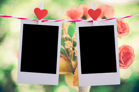 pack string: 2 Blank instant photo and red clippaper heart hanging on the clothesline with pink rose flower background. vintage tone.Designer concept.
